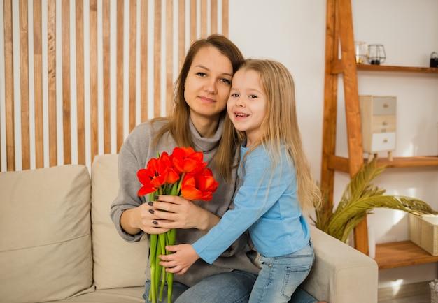 Moeder en dochter zitten op de bank met een boeket rode tulpen in de kamer