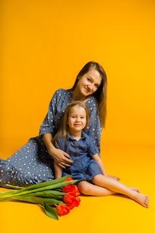 Moeder en dochter zitten op de grond met een boeket rode tulpen en kijken naar de voorkant op een gele muur