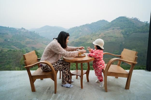 Moeder en dochter zitten op de houten tafel en drinken hete groene thee bij uitzicht op de bergen