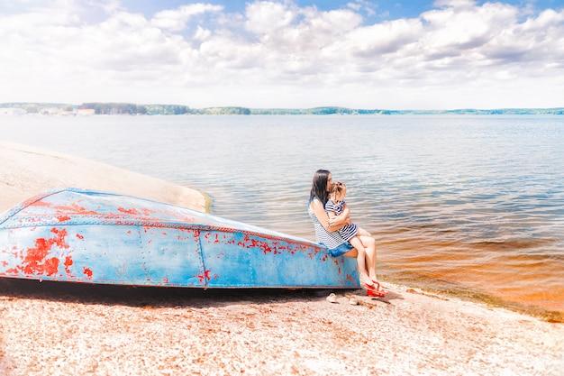 Moeder en dochter zitten op de oude boot op het meer