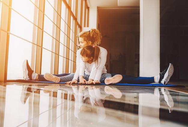 Moeder en dochter zitten op de vloer doen yoga