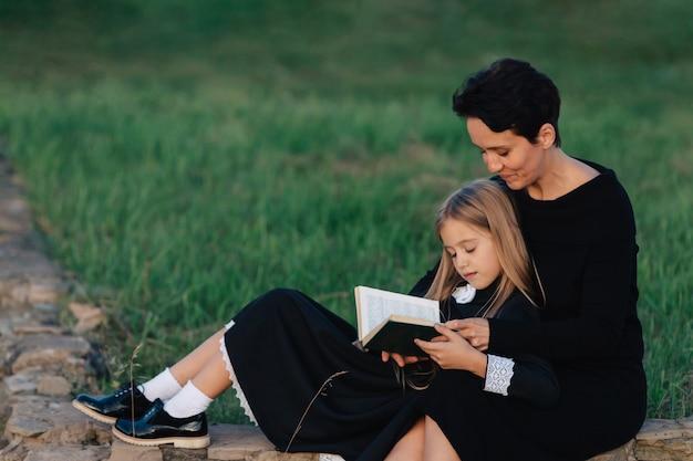Moeder en dochter zitten op een stenen bank en lezen een boek. vrouw met een kind in zwarte jurken.