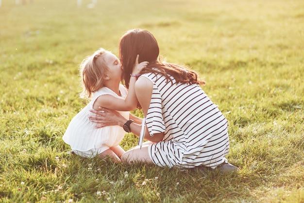 Moeder en dochter zitten op het gras van het veld en kussen elkaar
