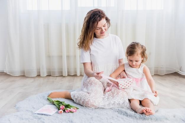 Moeder en dochter zitten op tapijt met geschenkdoos; bloemen en wenskaart