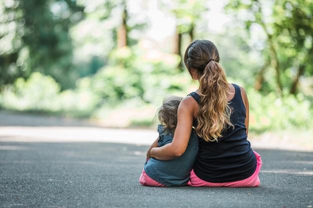 Moeder en dochter zitten samen in een park