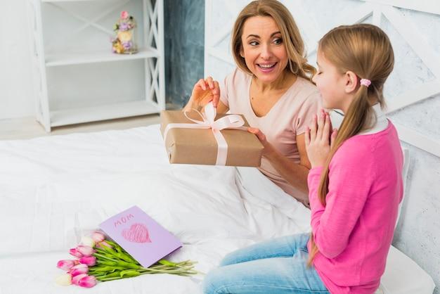 Moeder en dochter zittend op bed met cadeau