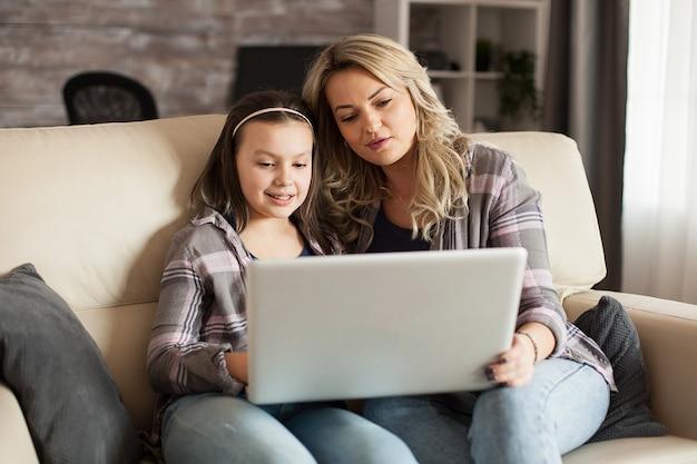 Moeder en dochter zittend op de bank in de woonkamer kijken naar een film op laptop.