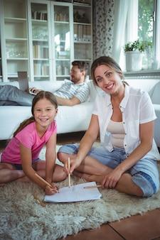 Moeder en dochter zittend op de vloer en tekenen