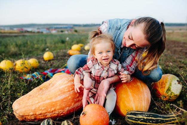 Moeder en dochter zittend op pompoenen