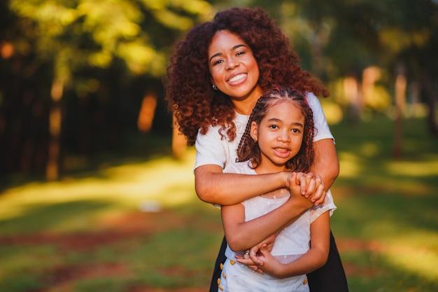 Moeder en dochterafro in het park