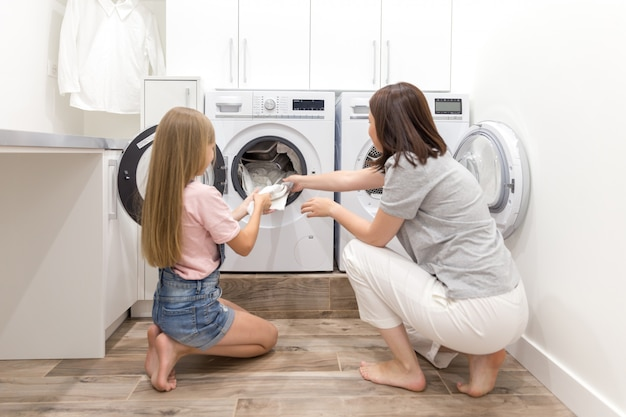 Moeder en dochterhelper in wasruimte dichtbij wasmachine en droger die schone kleren uittrekken