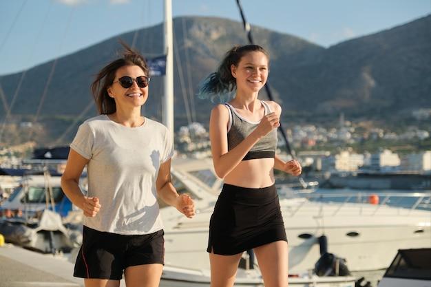 Moeder en dochterjogging die samen bij kustpromenade lopen