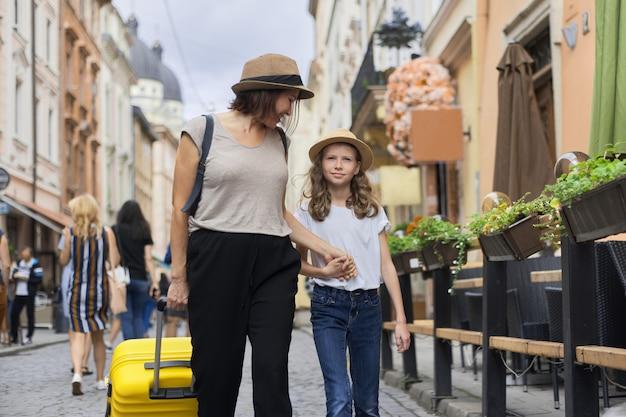 Moeder en dochterkind reizende toeristen met koffer op de straat van een oude toeristenstad