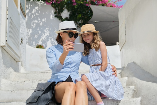 Moeder en dochterkindzitting op de witte stappen met smartphone