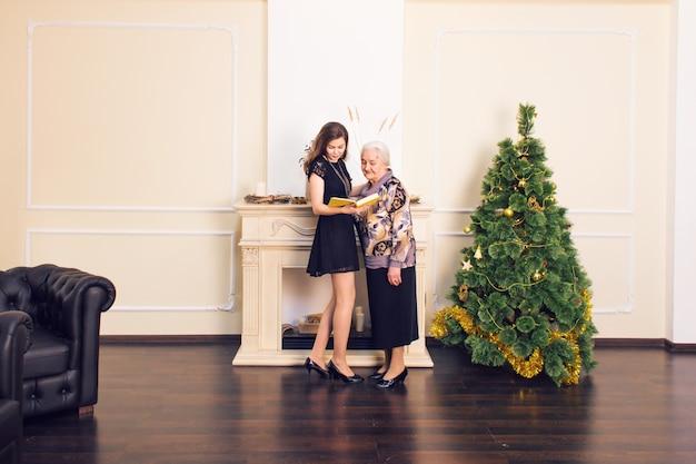 Moeder en dochterlezingsboek tegen kerstboom.
