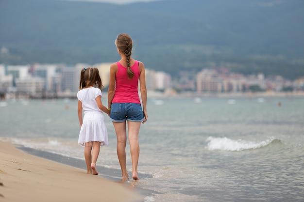 Moeder en dochtermeisje die samen op zandstrand lopen in zeewater