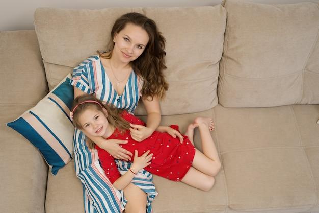 Moeder en dochterportret dat op bank ligt