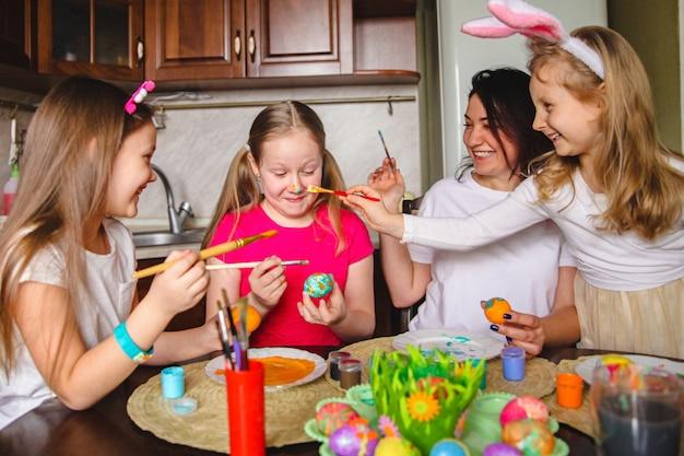 Moeder en dochters die bezig zijn met het kleuren van paaseieren, dwaas om de neus van het meisje te bevuilen.