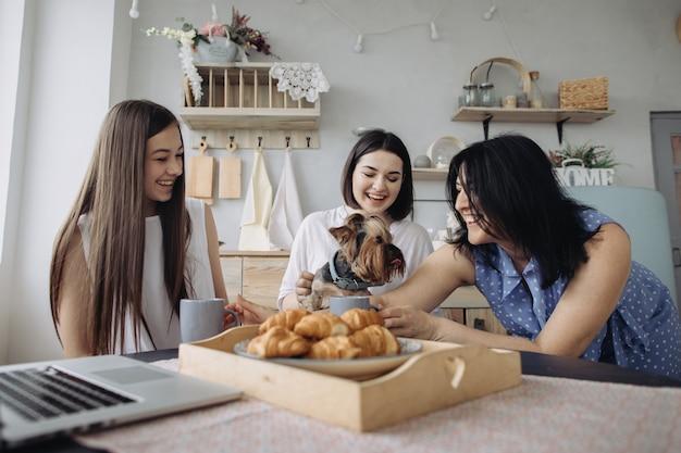 Moeder en dochters die en croissants in de keuken spreken eten