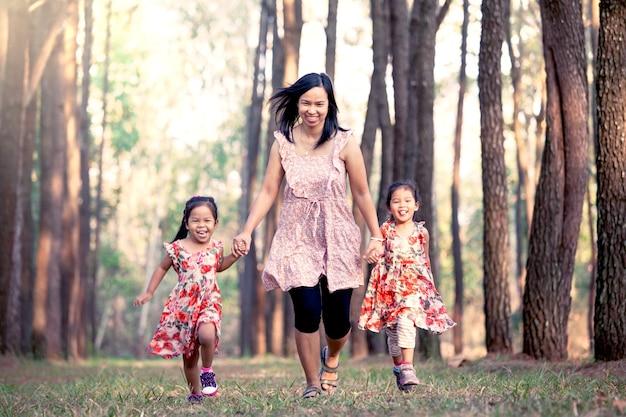 Moeder en dochters die hand houden en samen in het park in uitstekende kleurentoon lopen