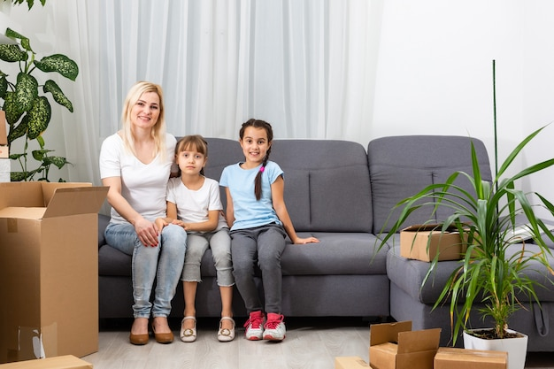 Moeder en dochters die thuis kartonnen dozen inpakken