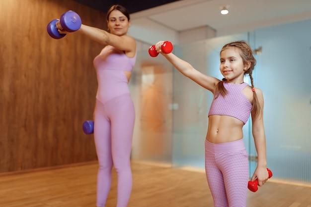 Moeder en dochters doen oefening met halters in de sportschool, fitnesstraining. moeder en klein meisje in sportkleding, gezamenlijke training in sportclub