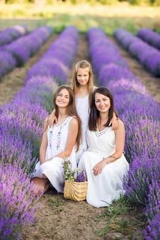 Moeder en dochters in een lavendelveld. zomerfoto in paarse kleuren.