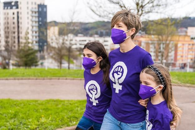 Moeder en dochters lopen over straat en dragen een paars t-shirt met het symbool van werkende vrouwen op internationale vrouwendag, 8 maart, en dragen een masker voor de coronavirus-pandemie