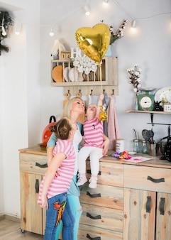 Moeder en dochters met hartballon in keuken
