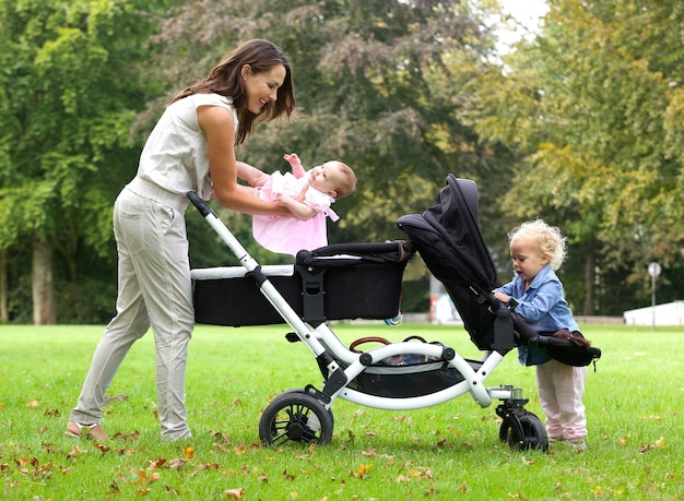 Moeder en dochters met kinderwagen buitenshuis