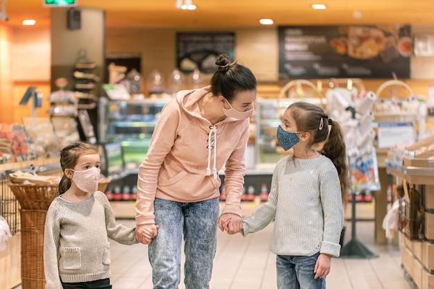 Moeder en dochters winkelen in de winkel in maskers tijdens quarantaine vanwege de pandemie van het coronavirus.
