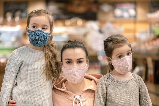 Moeder en dochters winkelen in maskers in de winkel tijdens quarantaine vanwege de coronavirus-pandemie van dichtbij.