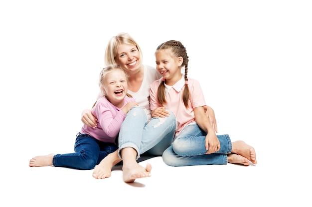 Moeder en dochters zitten en lachen. liefde en tederheid. geã¯soleerd op witte achtergrond.