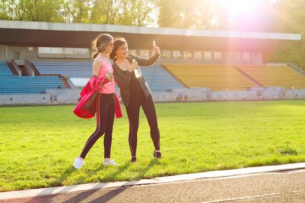Moeder en dochtertiener die na training bij stadion rusten