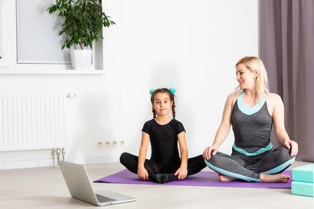 Moeder en dochtertje doen thuis gymnastiek op de mat. ze doen yoga. ze zijn leuk omdat ze een gelukkig gezin hebben. stelt dat ze naar de laptop kijken.