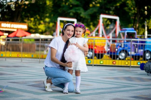 Moeder en dochtertje eten suikerspin en glimlachen van geluk in een pretpark in de zomer