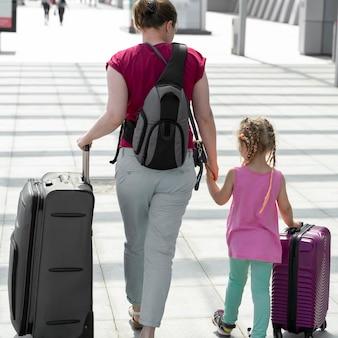 Moeder en dochtertje gaan met koffers naar de luchthaven. toerisme en reizen.