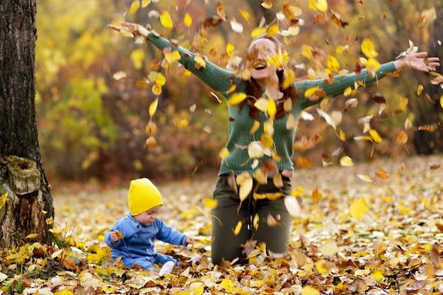 Moeder en dochtertje gooien gele bladeren in het herfstbos