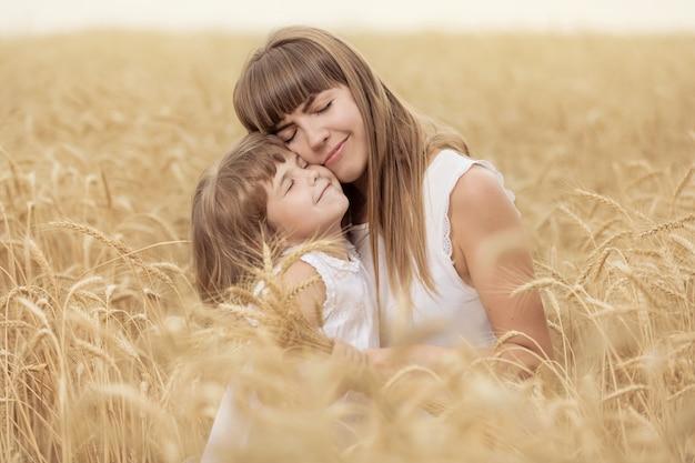 Moeder en dochtertje in een gele tarweveld, aartjes houden en knuffelen, hun ogen sluiten, concept, familie