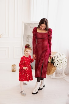 Moeder en dochtertje in rode jurken in een lichte slaapkamer