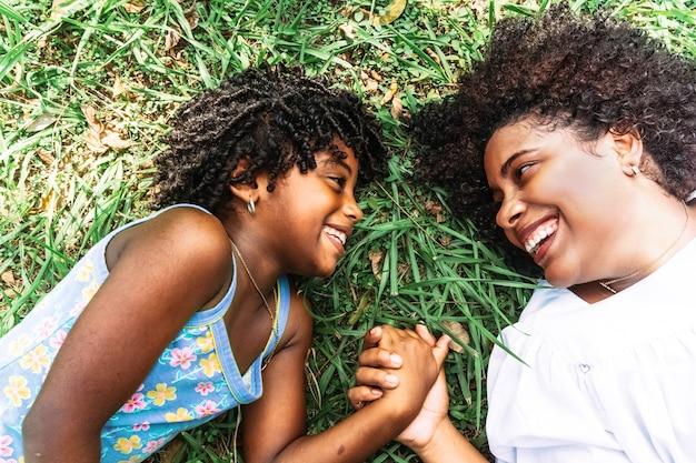 Moeder en dochtertje kijken elkaar glimlachend en gelukkig aan