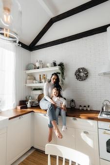 Moeder en dochtertje koken in de keuken en spelen. familie, geluk.