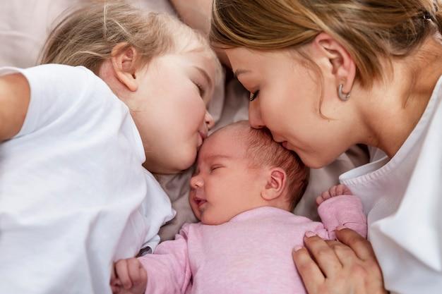 Moeder en dochtertje kussen een pasgeboren baby in roze kleding. geluk, liefde en tederheid. detailopname.