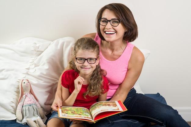 Moeder en dochtertje lezen boek thuis in bed.