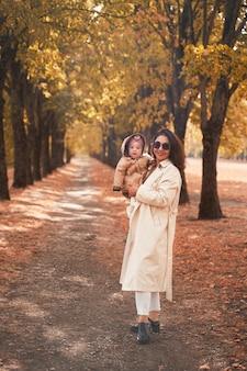 Moeder en dochtertje lopen in het herfstpark