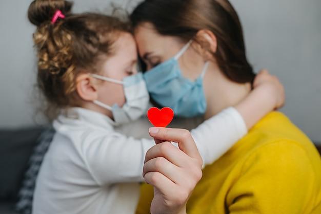 Moeder en dochtertje omarmen hechting, dragen een medisch gezichtsmasker, houden een rood hart vast om waardering te tonen en bedanken alle essentiële medewerkers tijdens de pandemie van covid-19. selectieve aandacht