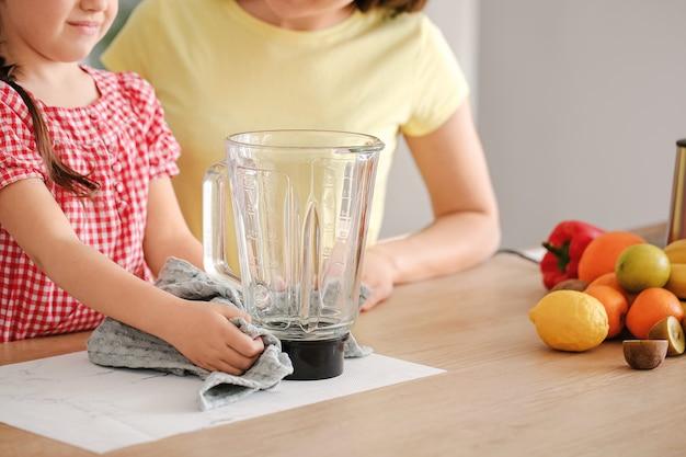 Moeder en dochtertje schoonmaak blender in keuken