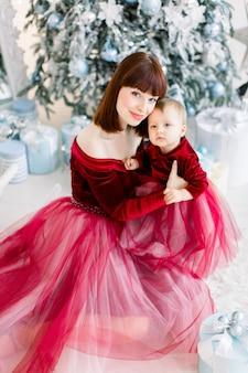 Moeder en dochtertje, zittend op de achtergrond van de kerstboom