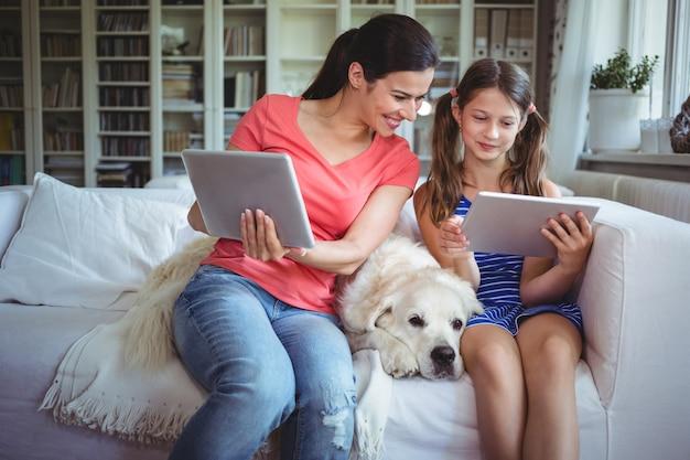 Moeder en dochterzitting met huisdierenhond en digitaal gebruiken
