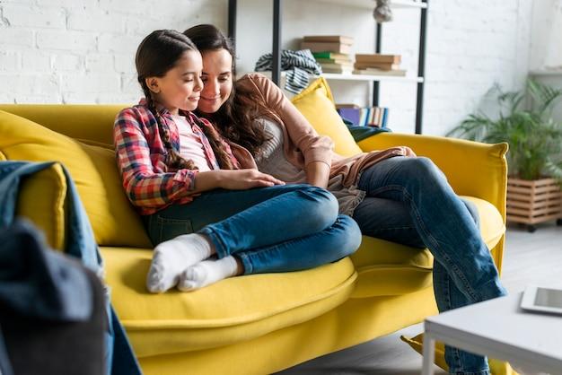 Moeder en dochterzitting op gele bank